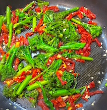 broccolini and sun dried tomatoes on carrot ribbon pasta